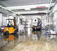 Concreted high gloss seal coats industrial floor with large tanker truck and forklift casting reflection across.