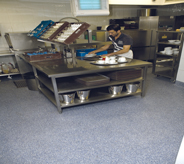 Deli worker preps food on grey floor.