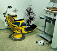 Dental chair on green flooring.