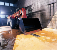 Oversized bulldozing truck sits atop durable orange colored flooring.