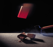 A brick falls atop swinging hammer to demonstrate floor coating durability.