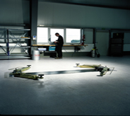 Car lift rests center while mechanic in foreground stands atop durable garage floor system.