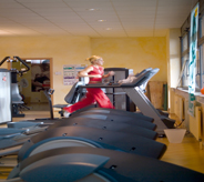 Woman jogs on treadmill that sits atop a fitness center floor.