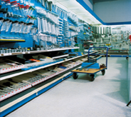 Highly trafficked walkway area of hardware store displays loaded rolling cart atop grey covered flooring.