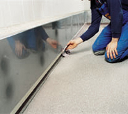 Floor installer works to complete his commercial projects by applying finishing touches to base trim.