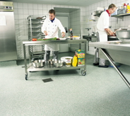 Cook preps food in kitchen area on cart that can move easily across floor.