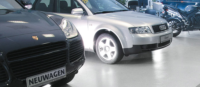 Cars parked on a dealership gray single color floor.
