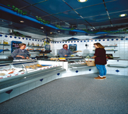 A grocery store shopper stands on flake floor while selecting meat for dinner.