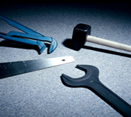 Several hand tools lie atop a blue grey hangared flooring system.
