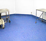 Hospital clean flooring with cart and bed on it