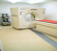 A hospitals x-ray machine sits center of cream yellow colored flooring room.
