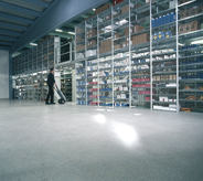 Grey sealed concretes glimmer in light inside industrialized warehouse.