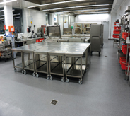 Large industialed stainless steel coated kitchen counter tops rest atop grey floor system.