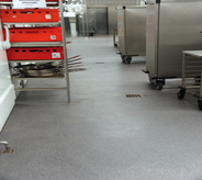 Multiple floor drains adourn grey coated industrialed kitchen.
