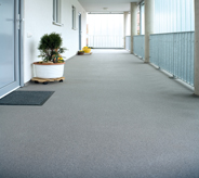 Outdoored industry flooring protects long exterior walkway of hotel.