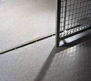 Sliding jailed gate casts shadow across light grey floor system.