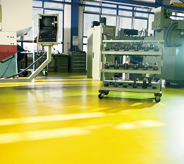 A bright yellow floor in a machine shop.