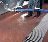 Worker attached large hose to stainless steel tank while standing atop maroon colored enhancing mma floor system.