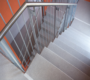 Stair lines with grey floor leading to motel rooms from lobby.