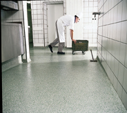 A non slippery flooring coat protects kitchen worker as he briskly moves a rolling bucket across open hallway.