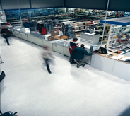 Patrons of large purchasing warehouse briskly move in seamless motion across non slip flooring.