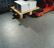 A loaded red pallet jack glides across a no skid flooring surface.