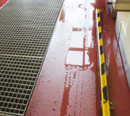 Outdoor waterproof flooring shows surface top moisture beading atop red colored car wash floor coating.