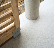 Grey seamless flooring surrounds wood rail and wide column with outdoor waterproofed protection.