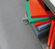 Brightly colored pharmaceutical carts stacked on grey floor.