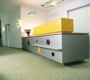 Lobby of pharmaceutical company has grey floor and yellow reception desk.