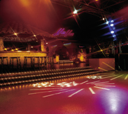 Resiliently lit dance floor reflects bright light effects in colorful patterns.