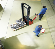 Commercial warehouse floorings displays resiliency as workers move heavy material with a pallet jack.