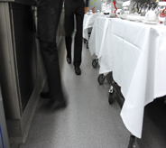 Restaurant waiters and waitresses hurriedly walk across grey colored flooring.