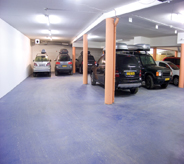 No seam blue flooring protects parked cars inside large community space garage.