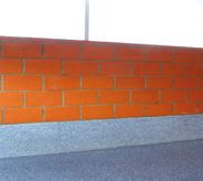 School accessway displays newly resurfaced self leveling floor system meeting red bricked wall.