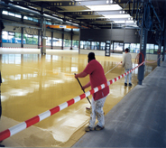 Professional floor resurfacing specialist spreads self leveling compound inside large industrial building.