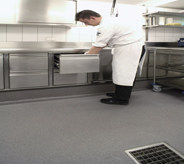 Chef preps in kitchen with slip resistant floor.