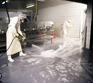 Worker pressure washes solvent resistant floor.