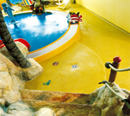 A concrete coated edifus copies fantasy isle look complete with stones and trees for interior kids play area.