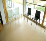 Open glass surrounds waiting room allowing sun light across area seating floor coating that is UV protected.