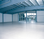 A bright white floor accents the open space in this large warehouse.
